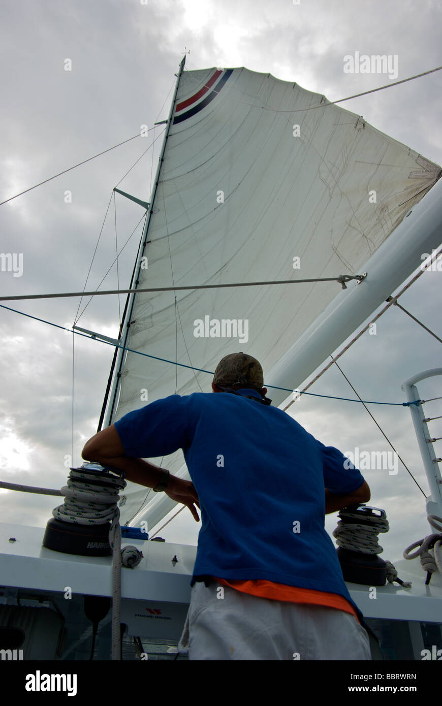 Catamaran charterboat skipper at helm watching storm clouds above mainsail while steering his course - Stock Image