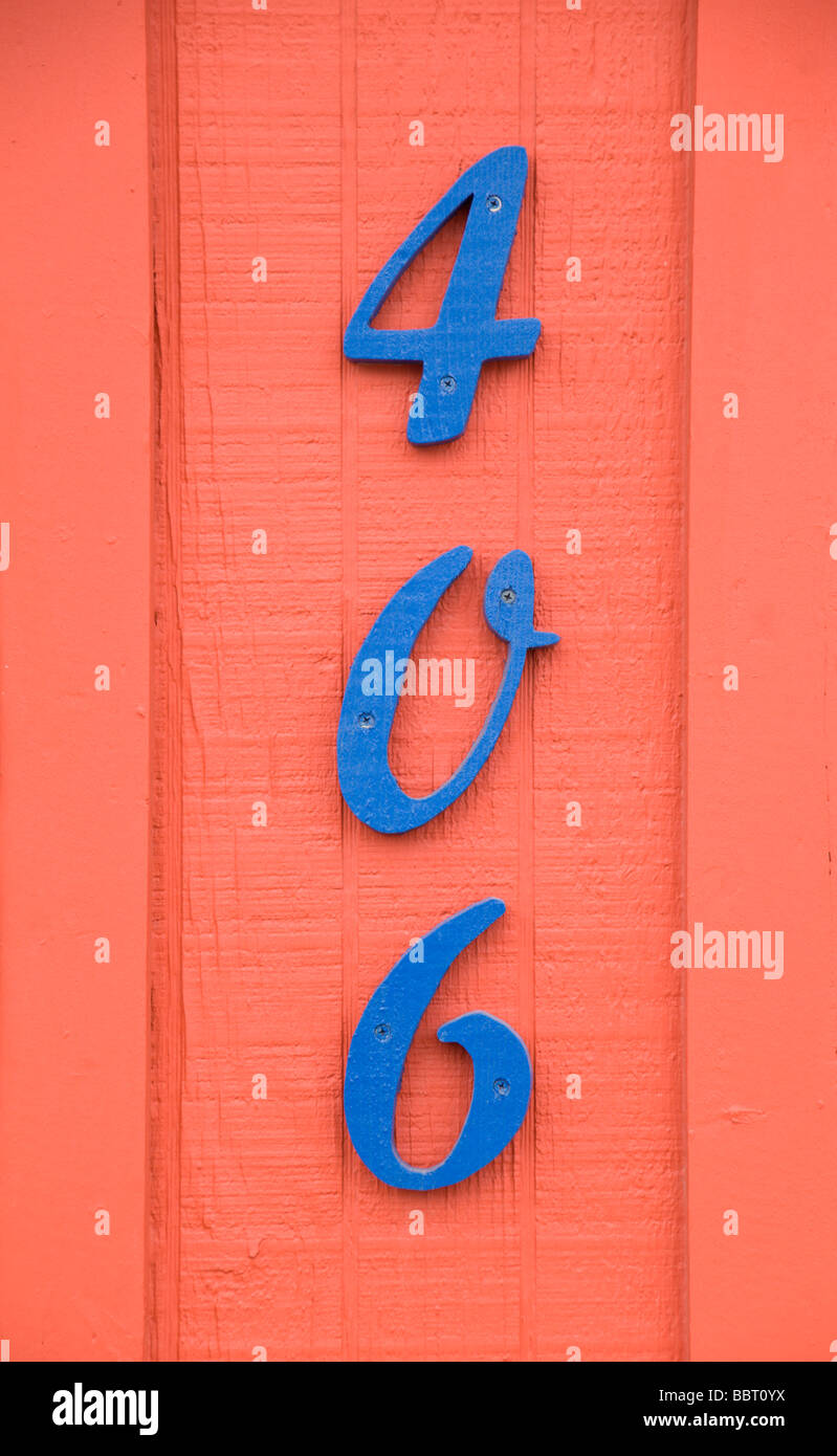 A blue address on a orange building can't be missed, in Carrizozo, New Mexico. - Stock Image