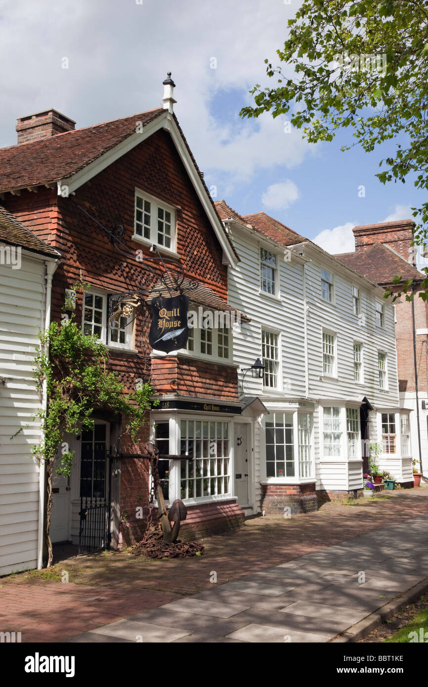 Small shops in 15th century tile hung and white clapboard buildings on High Street in Tenterden Kent England UK - Stock Image