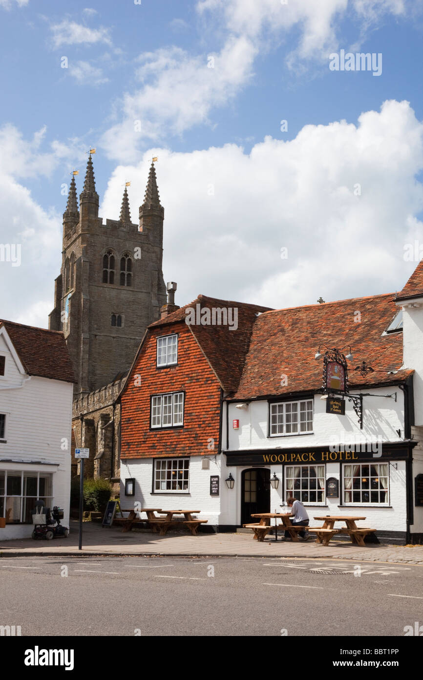 Tenterden Kent England UK The Woolpack hotel 15th century pub exterior and St Mildred s Parish Church clock tower - Stock Image