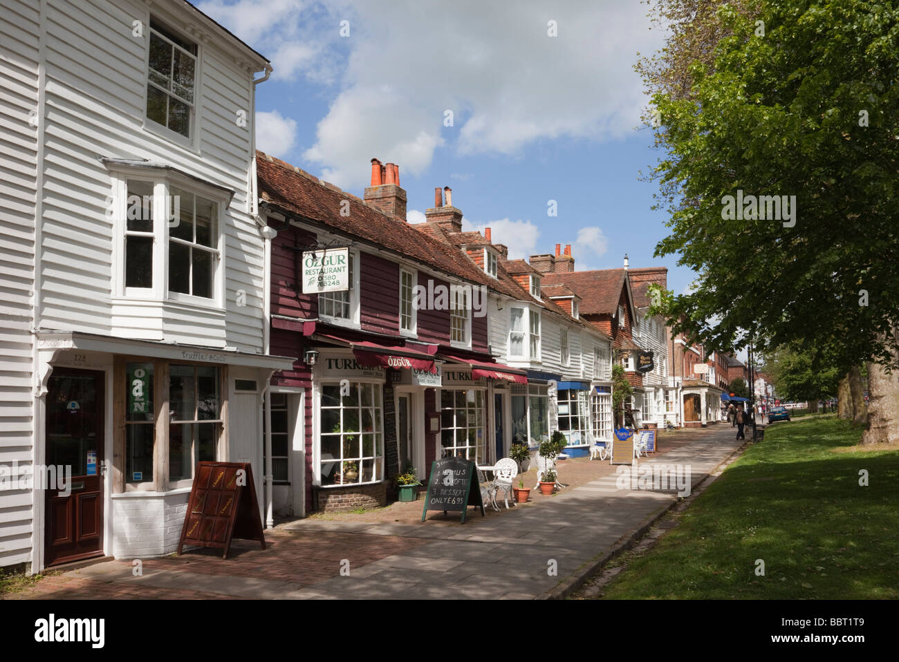 Tenterden Kent England UK  Small shops in 15th to 18th century buildings on tree-lined High Street in Wealden town - Stock Image