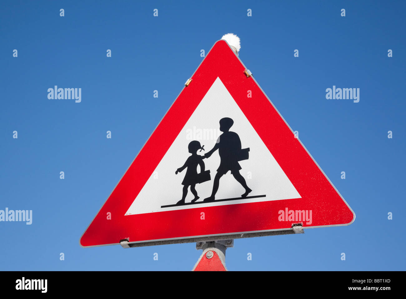 Triangular warning sign for children crossing road against blue sky background. UK Britain Europe - Stock Image