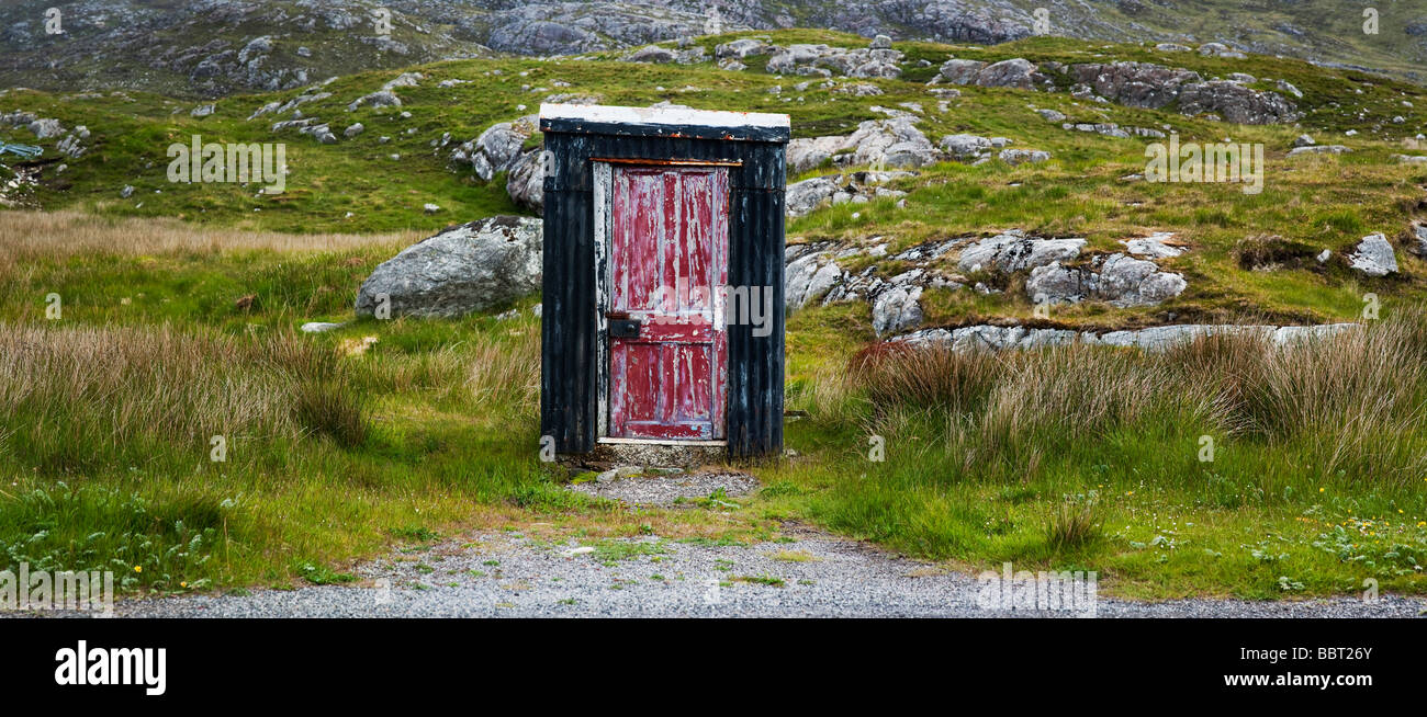 Remote tin hut with a weathered red wooden door, Near Tarbert, Isle of Harris, Outer Hebrides, Scotland - Stock Image