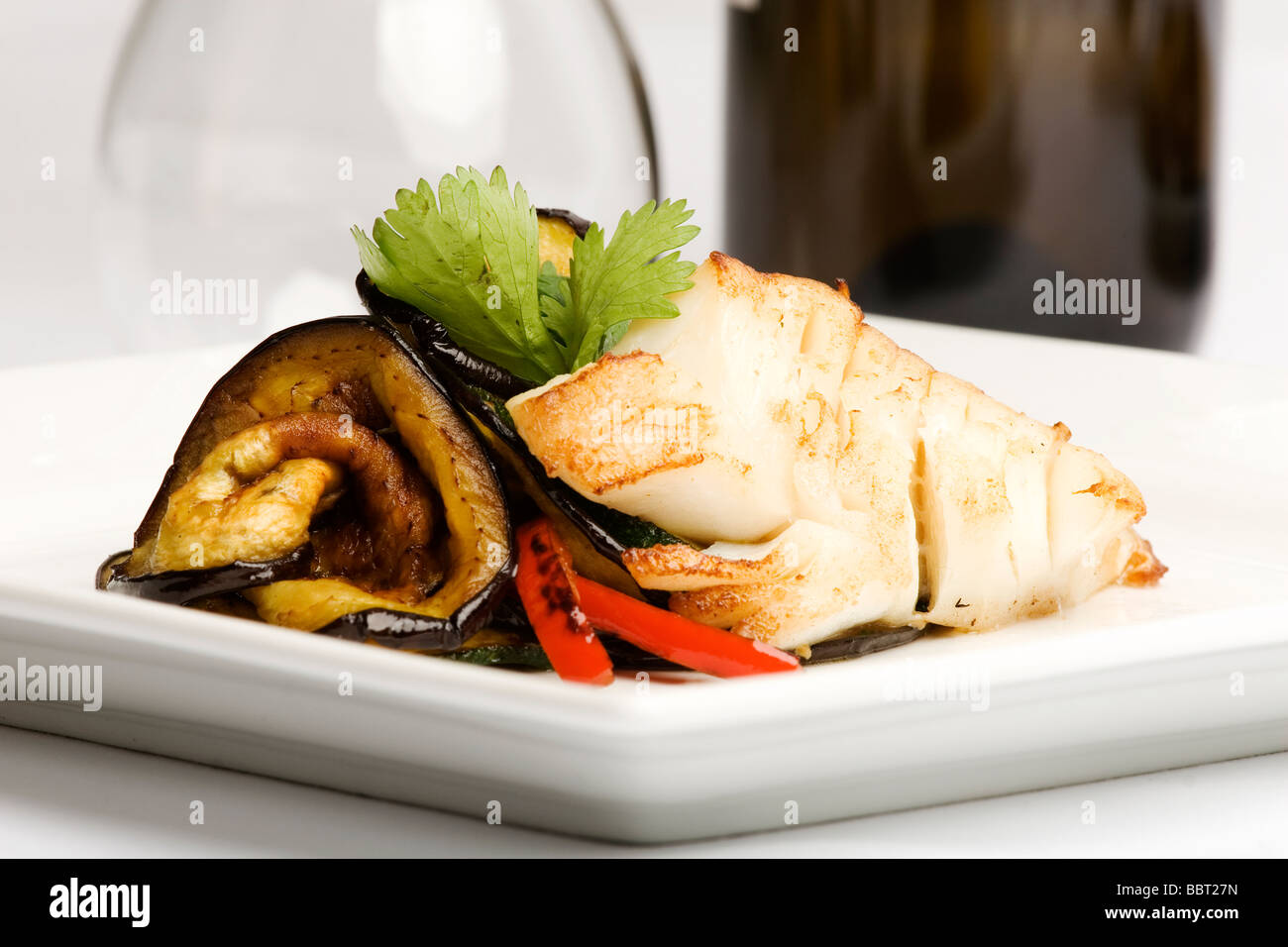 Baked cod with side of eggplant and peppers - Stock Image