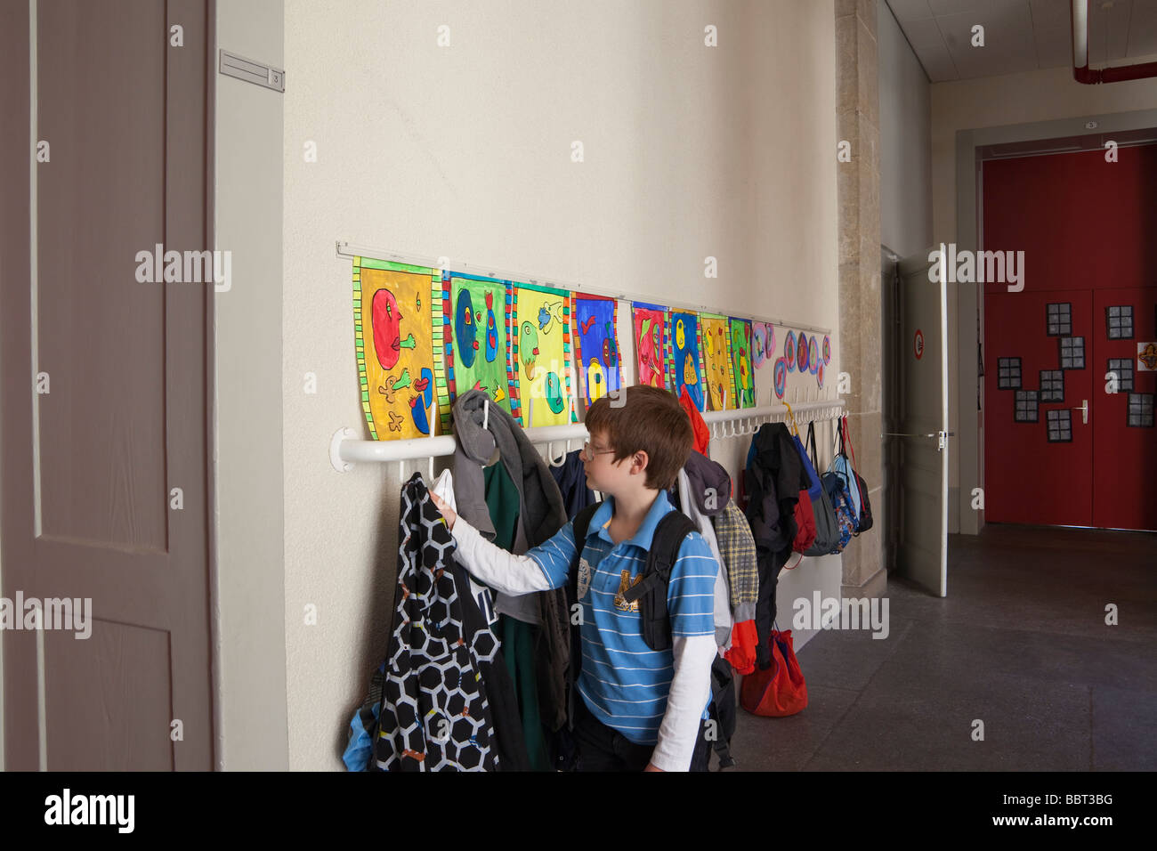 9 year old boy taking his coat off of a coat hook outside his classroom. Charles Lupica - Stock Image
