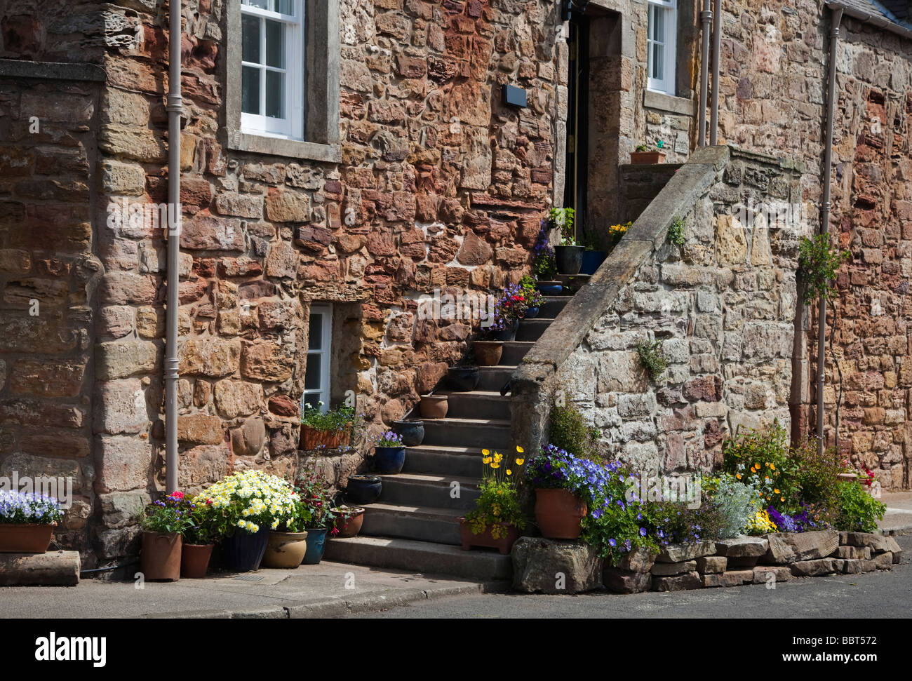 Traditional stone cottage with access stairway decorated with potted plants Crail Fife Scotland - Stock Image