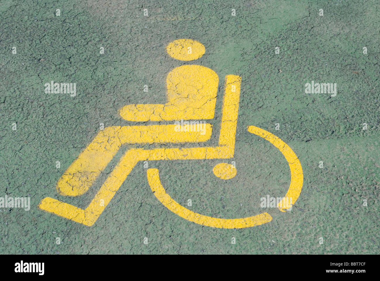 Painted yellow Handicap symbol on a parking space - Stock Image