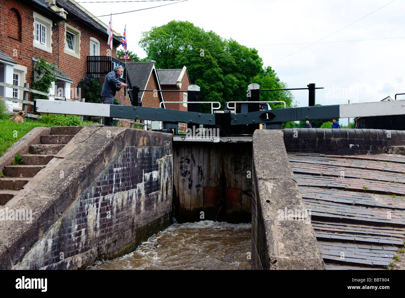 Lock keeper help the crew of a barge negotiate their way through the gates at Tyrley Locks on the Shropshire Union - Stock Image