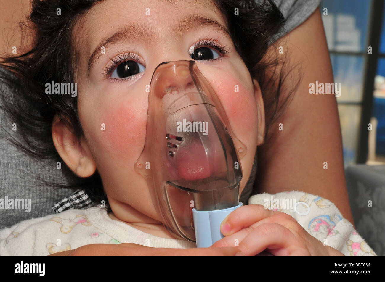 An Asthmatic child of 4 holds an inhaler on his face Model release available - Stock Image