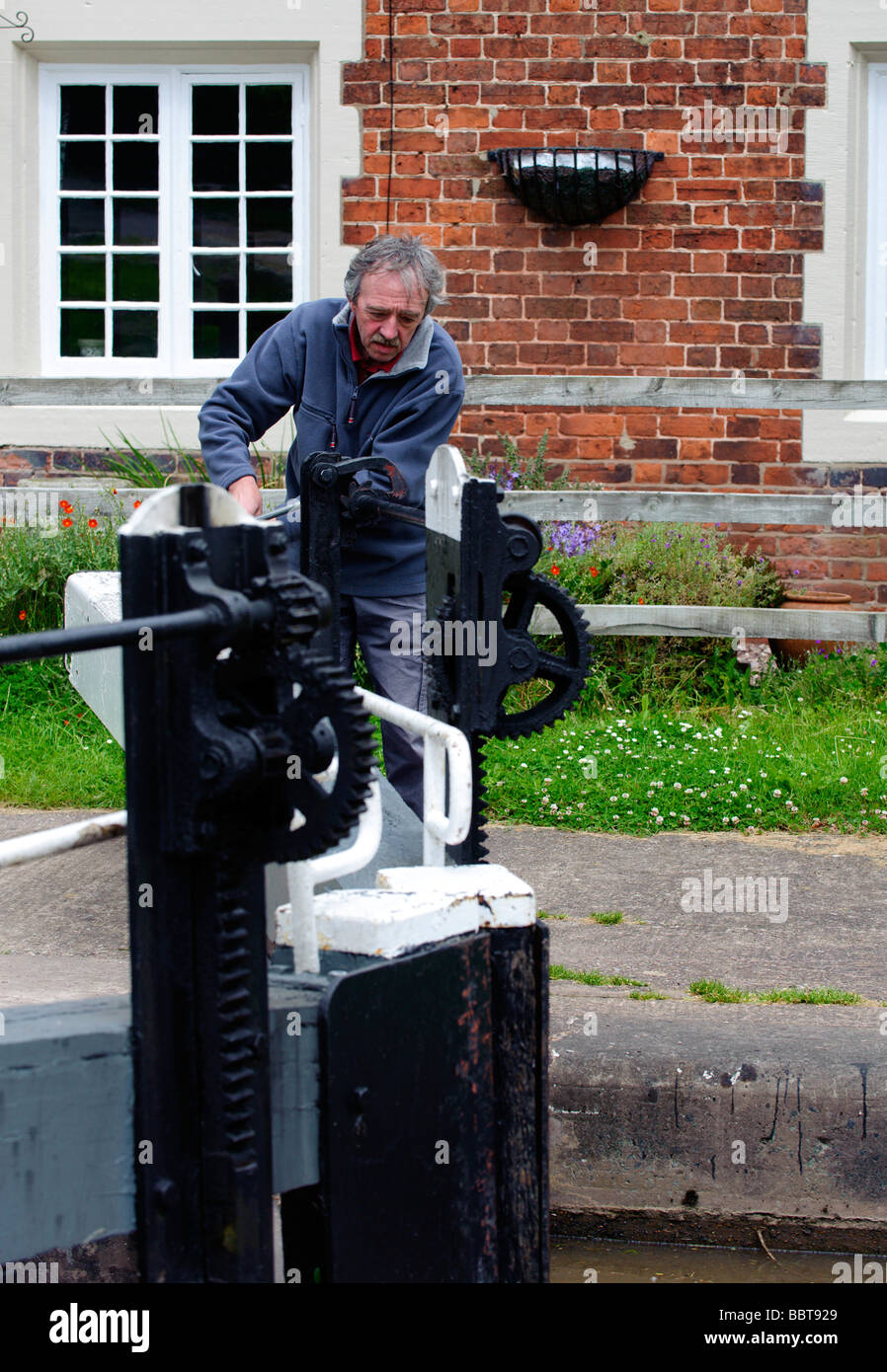 Lock keeper opening one of the Tyrley Lock gates Stock Photo