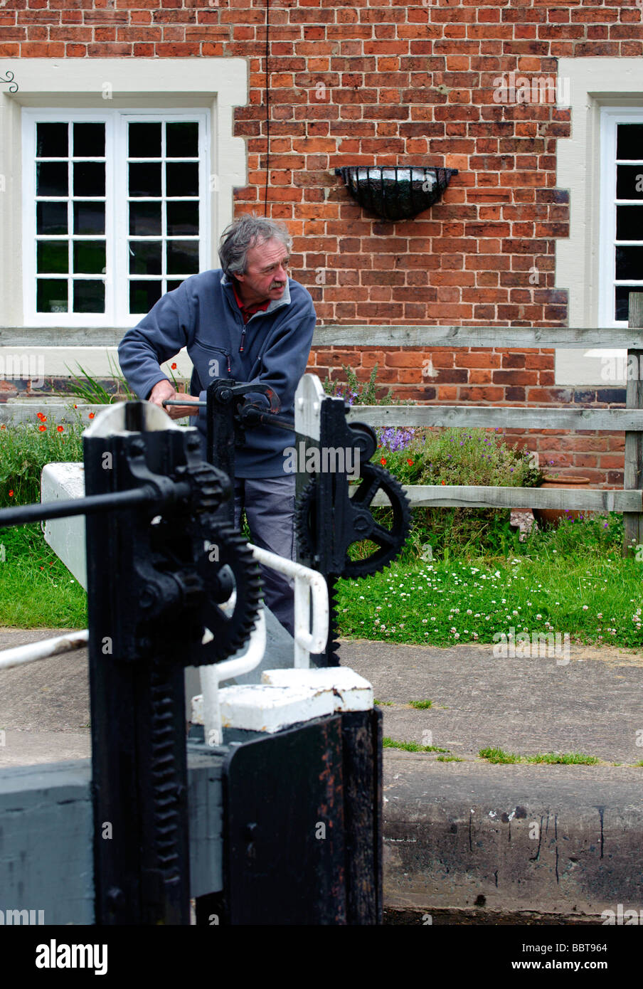 Lock keeper opening one of the Tyrley Lock gates - Stock Image