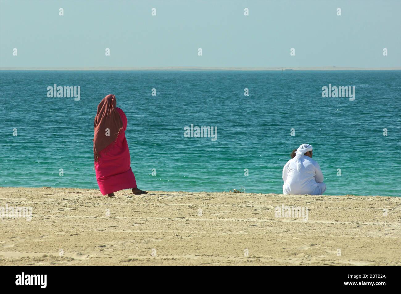 Dubai Arab couple on Jumeirah beach - Stock Image