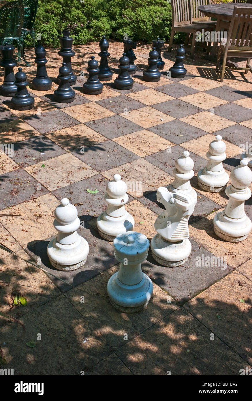 Chess pieces on an outdoor patio game - Stock Image