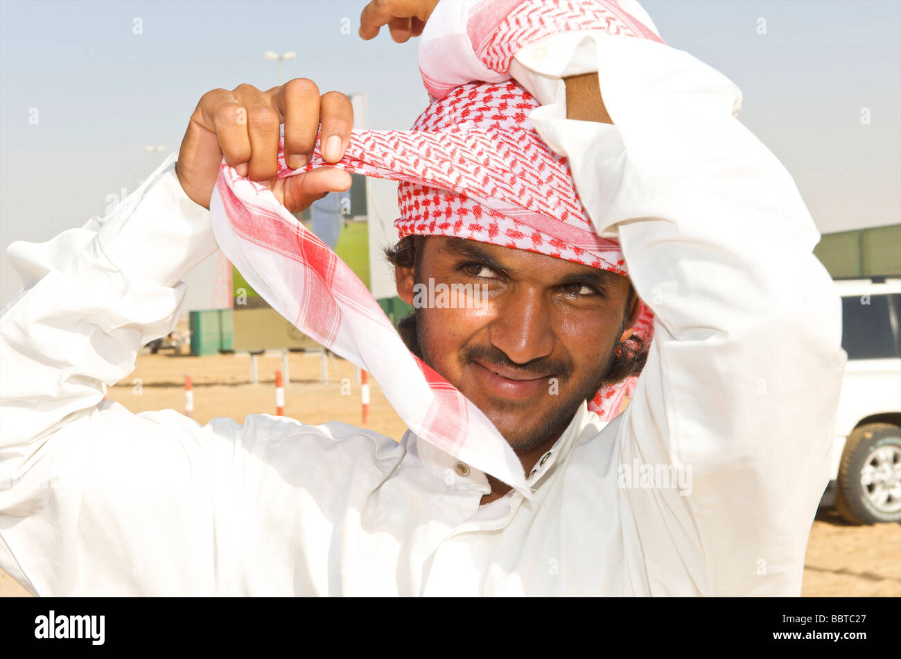 Dubai demonstration of how to attach a headscarf - Stock Image