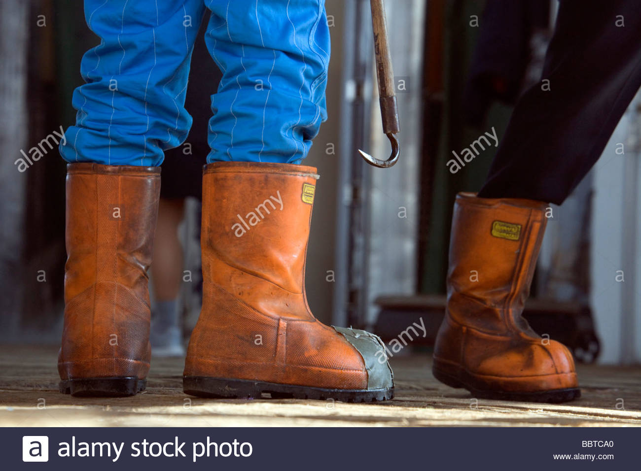heavy work boots of Tuna fish transporters - Stock Image