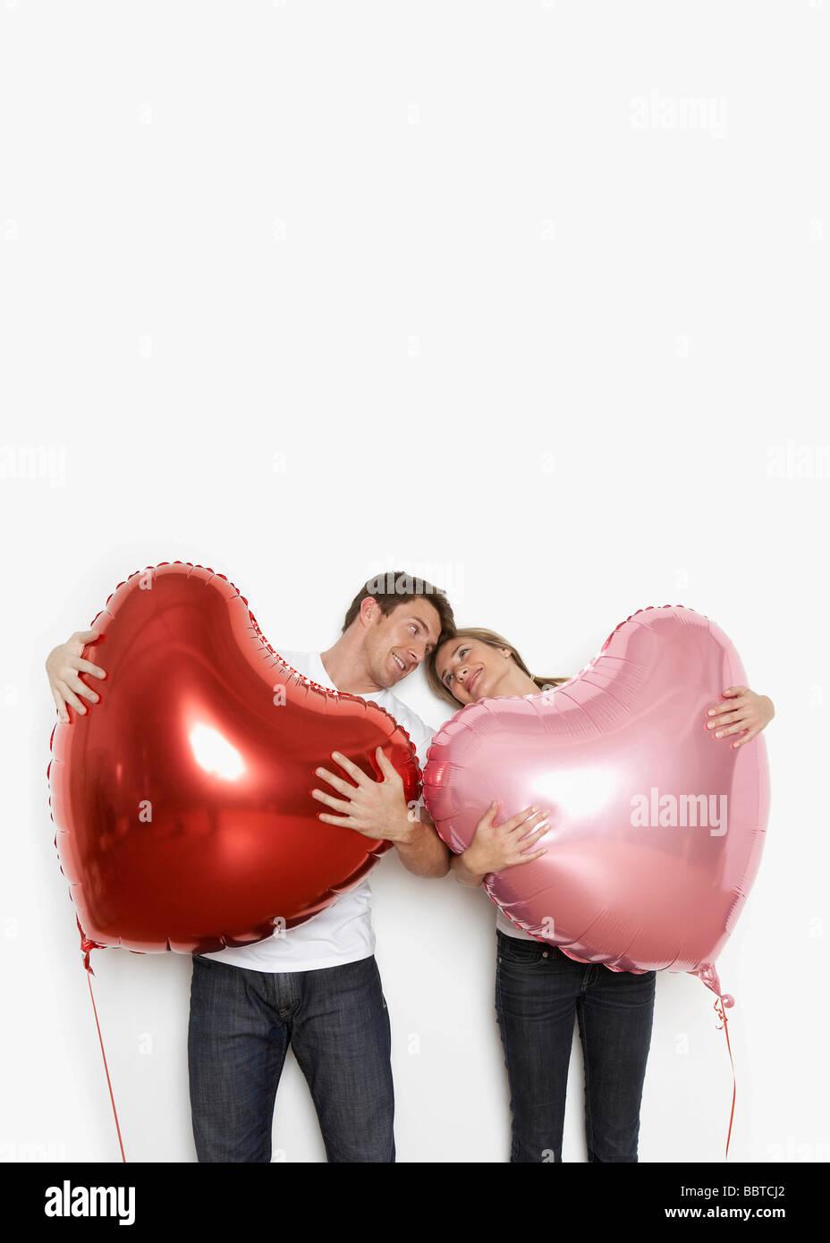 Couple holding heart balloons - Stock Image