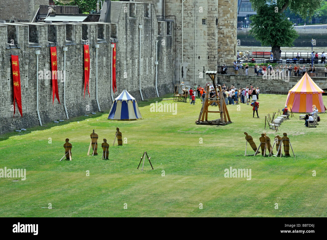 Tower of London summertime tourist activities below the walls River Thames beyond - Stock Image