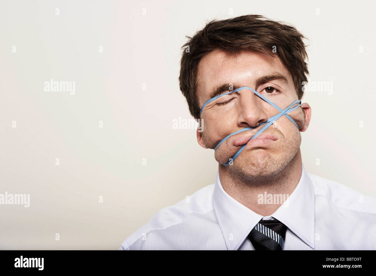Business man with rubber bands on face - Stock Image