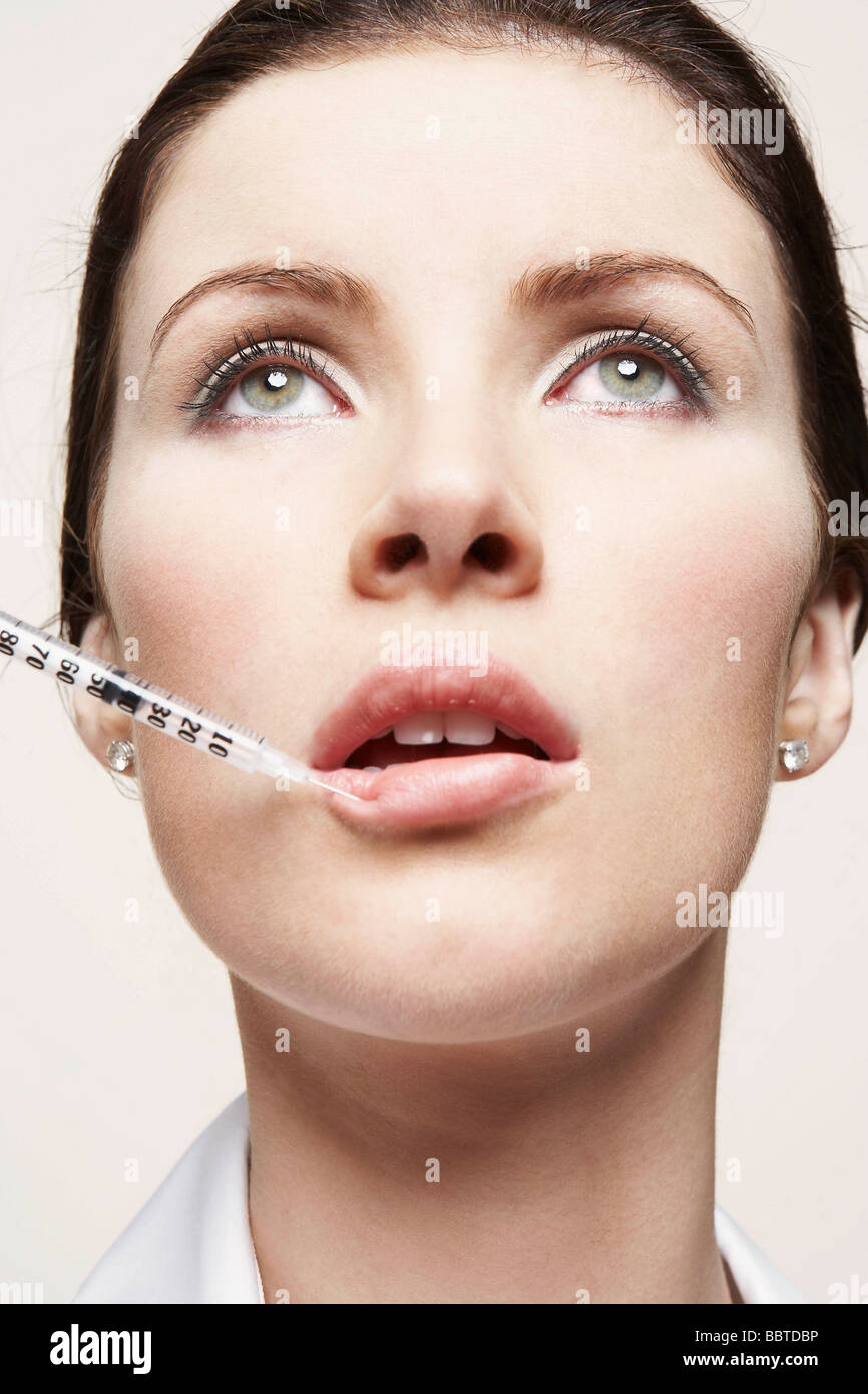 Woman with hypodermic syringe - Stock Image