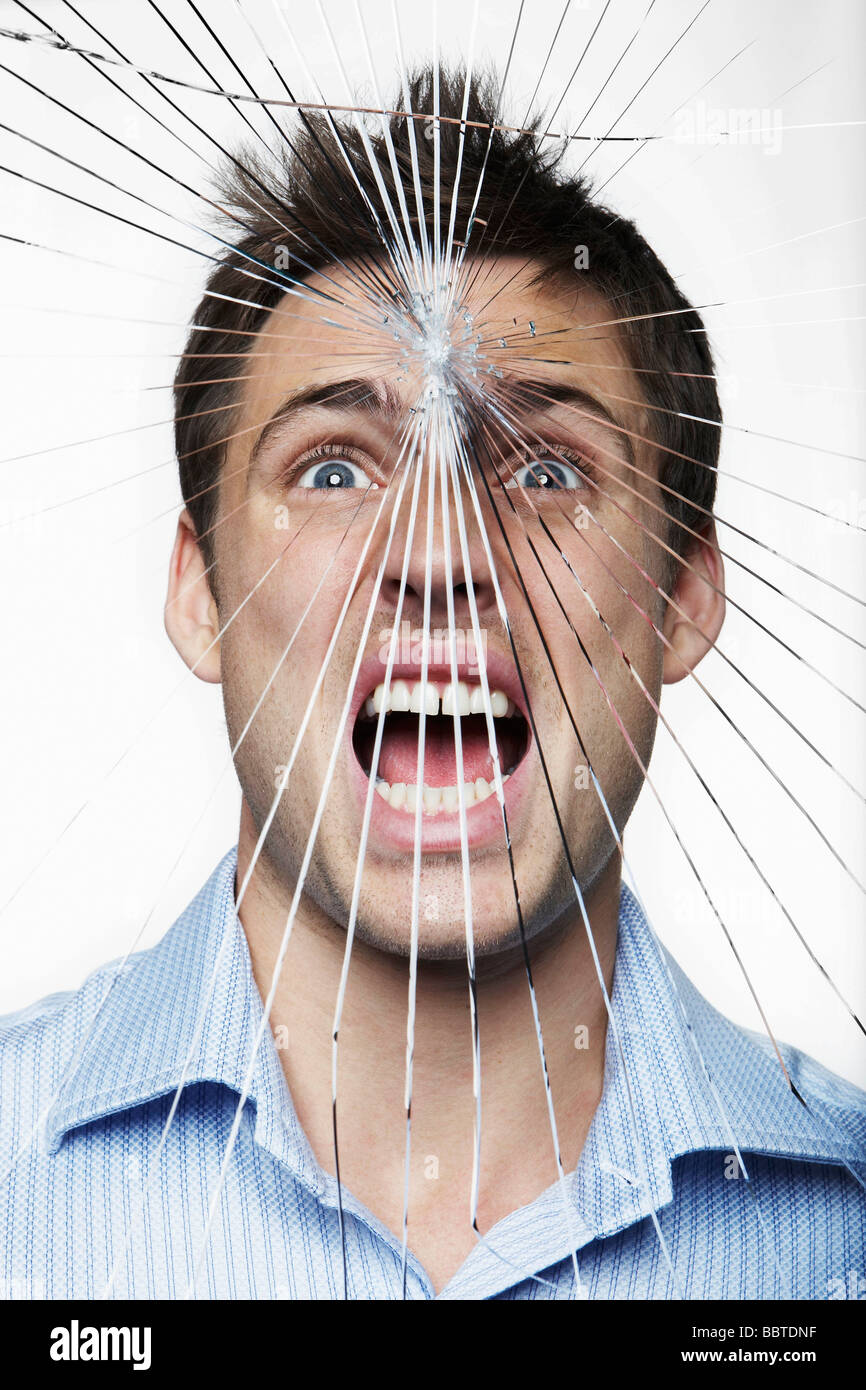 Young man behind cracked glass - Stock Image