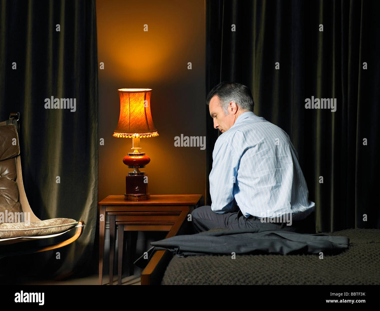 Man sitting on bed with back to camera Stock Photo