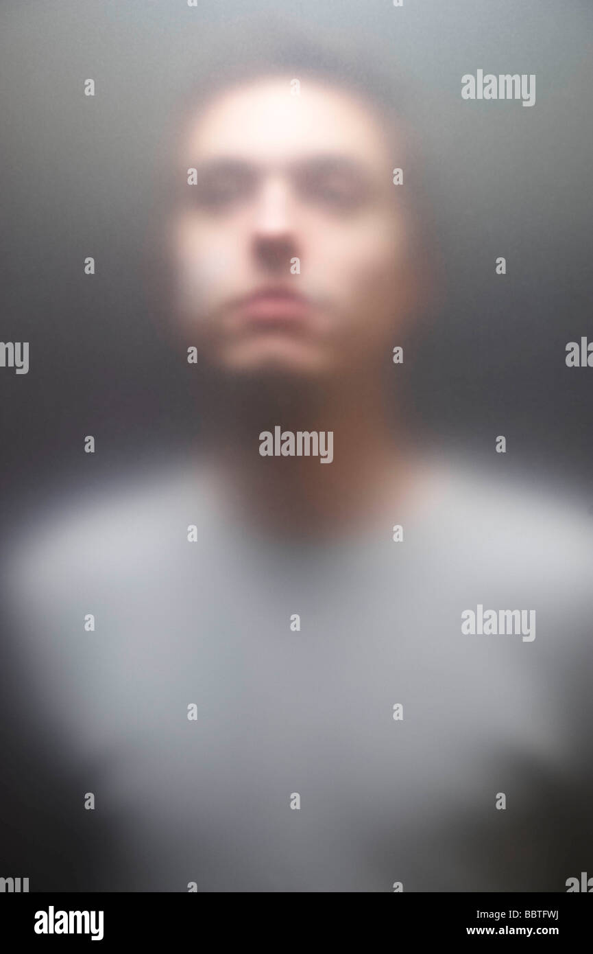 Young man behind frosted screen - Stock Image