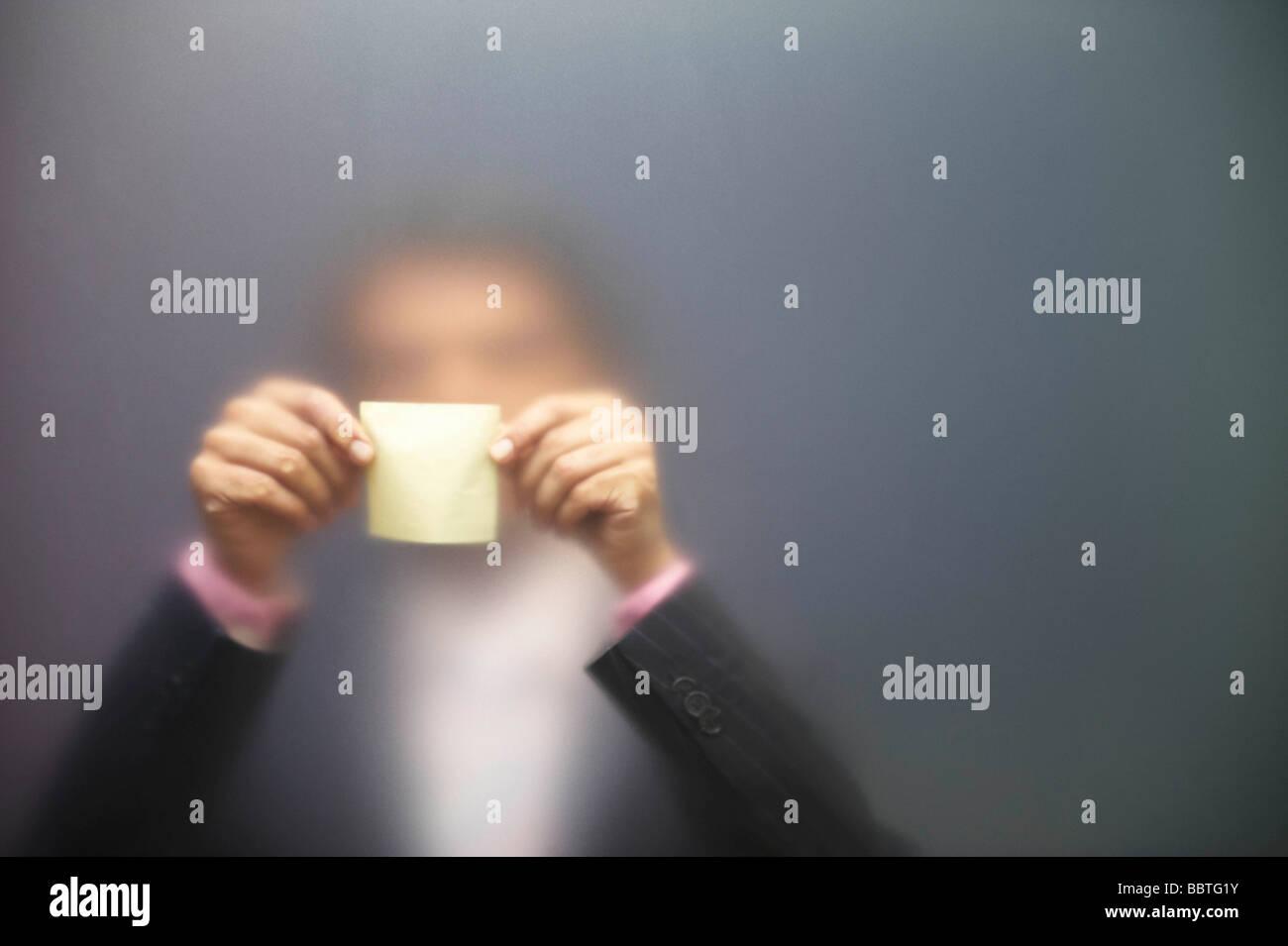 Man sticking note on frosted screen - Stock Image