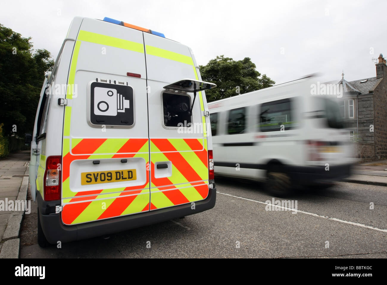 A Safety Camera van parked at the side of a road in Aberdeen, Scotland, UK, with a blurred minibus driving by - Stock Image