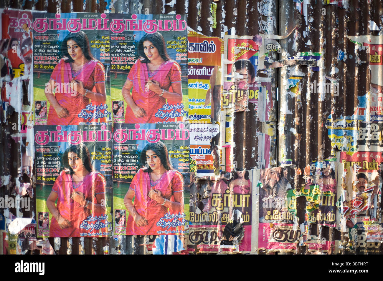 Posters stuck on corrugated iron fence in city centre, Madurai, Tamil Nadu, India Stock Photo