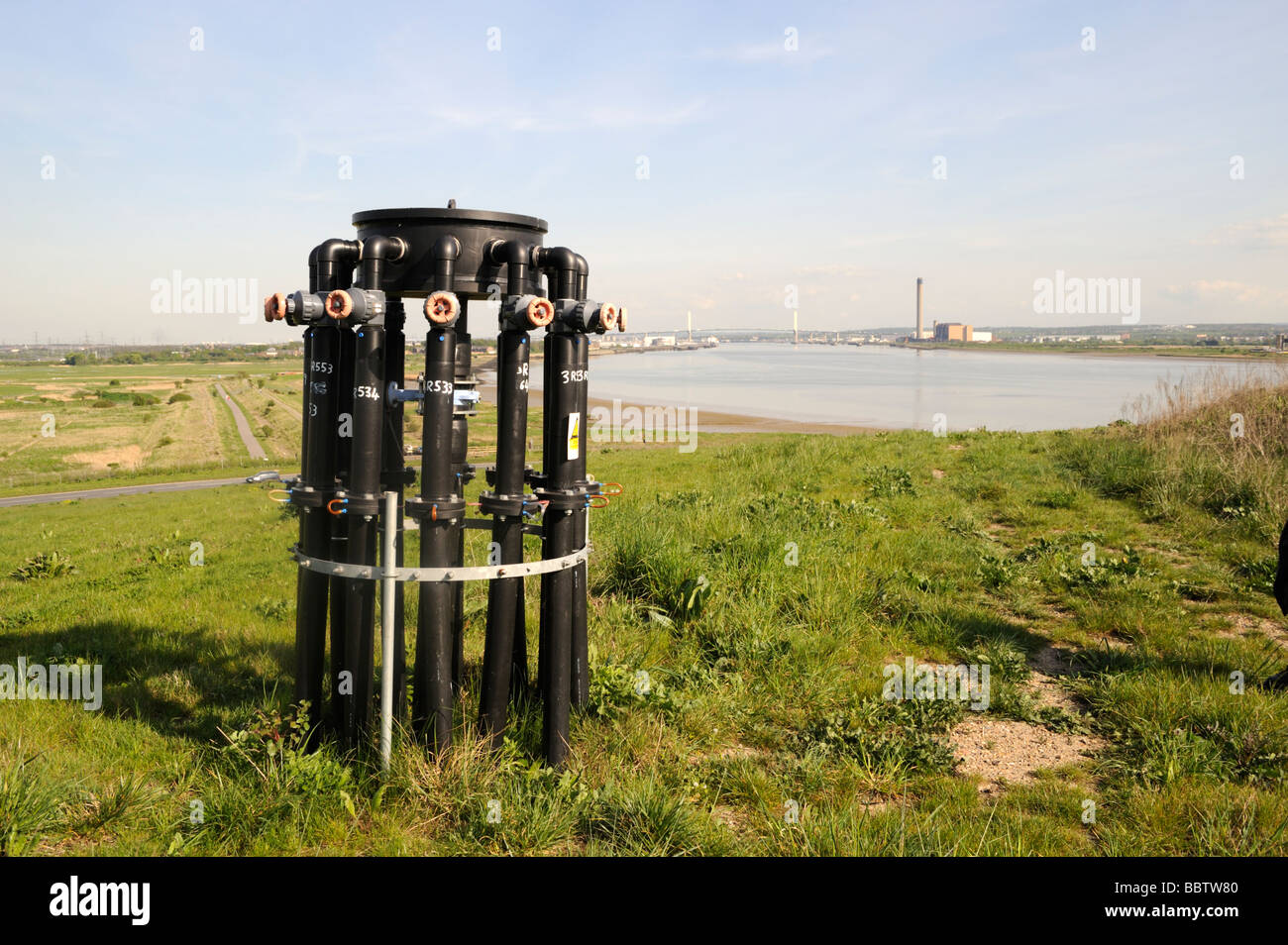 Rainham Essex,landfill site,pipes for siphoning methane gas to local power plant,view across Thames to Kent,UK - Stock Image