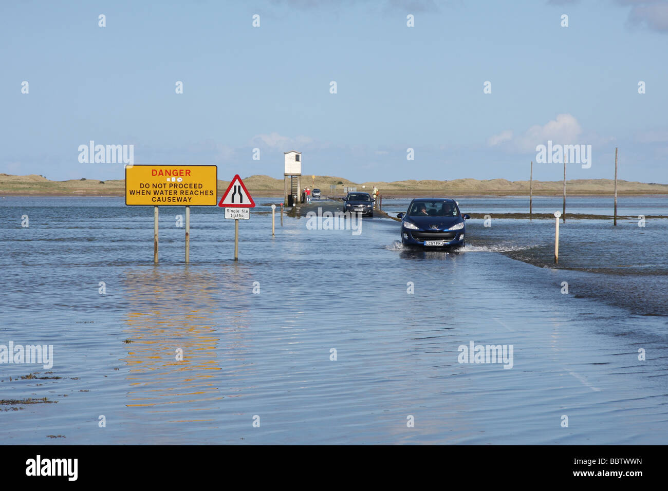 Car crossing causeway to Beal from Holy Island, as tide ebbs - Stock Image