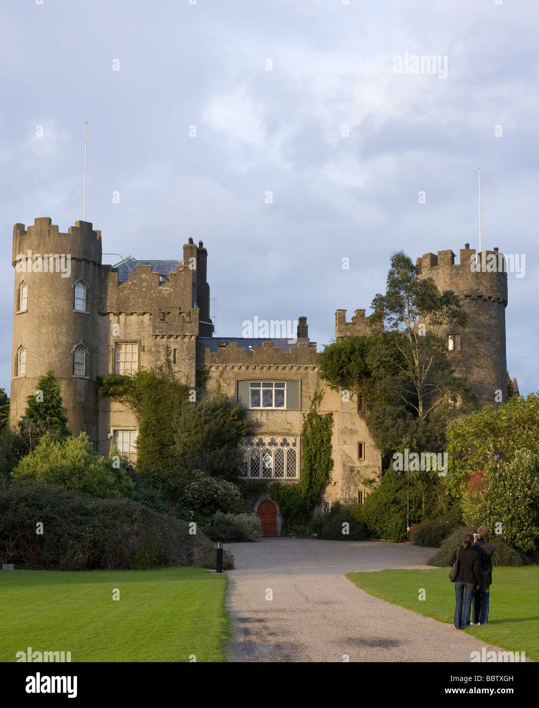 Malahide Castle with Tourists. The turreted castle at Malahide, seat of the Talbots is photographed by a pair of - Stock Image