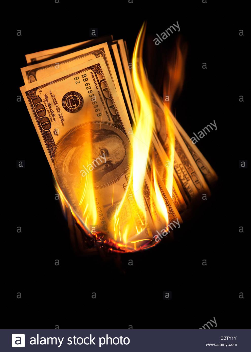 Bundle of US $100 bills burning. - Stock Image