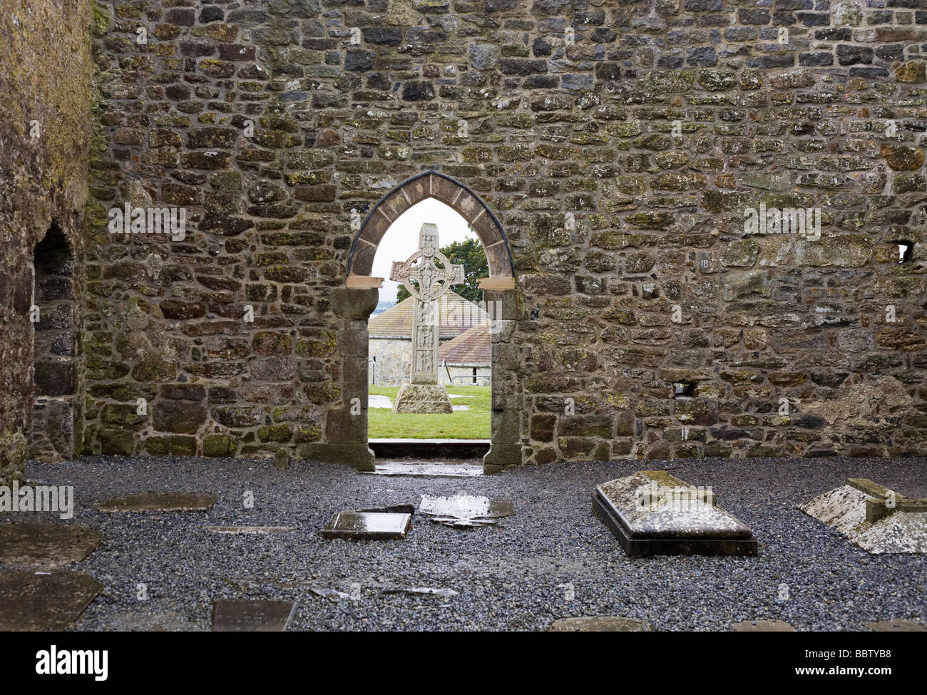 High Cross and Wall. Cross of the Scriptures c908 framed by a doorway of the Temple Coghlan Cathedral or Temple - Stock Image