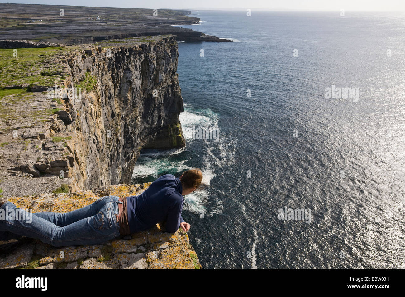 High View, Crashing Waves. A young woman leans over the 100 meter cliff at Dun Angus to take in the spectacular - Stock Image