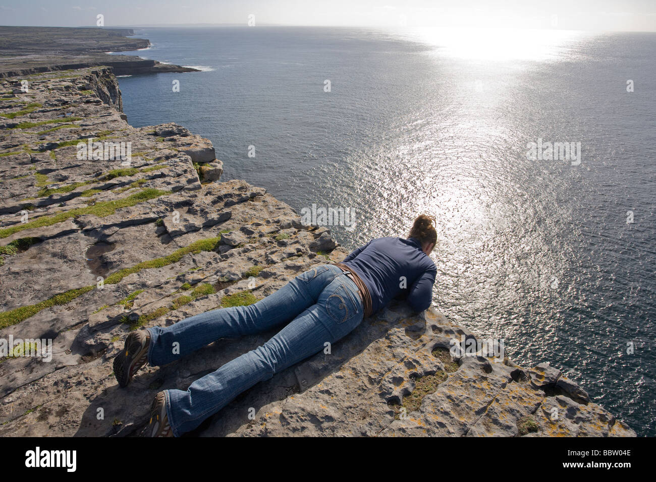 At the Edge. A young woman, echoing the lines in the rock, leans over the 100 meter cliff at Dun Angus to take in - Stock Image