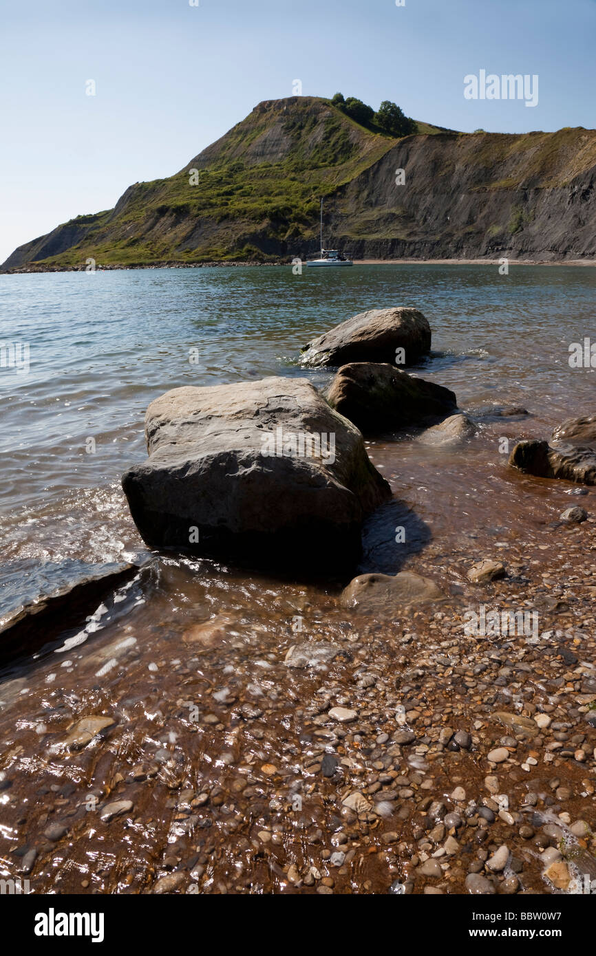 Rocks on beach and rugged landscape in distance on warm summer's day Chapman's Pool, Dorset, England - Stock Image
