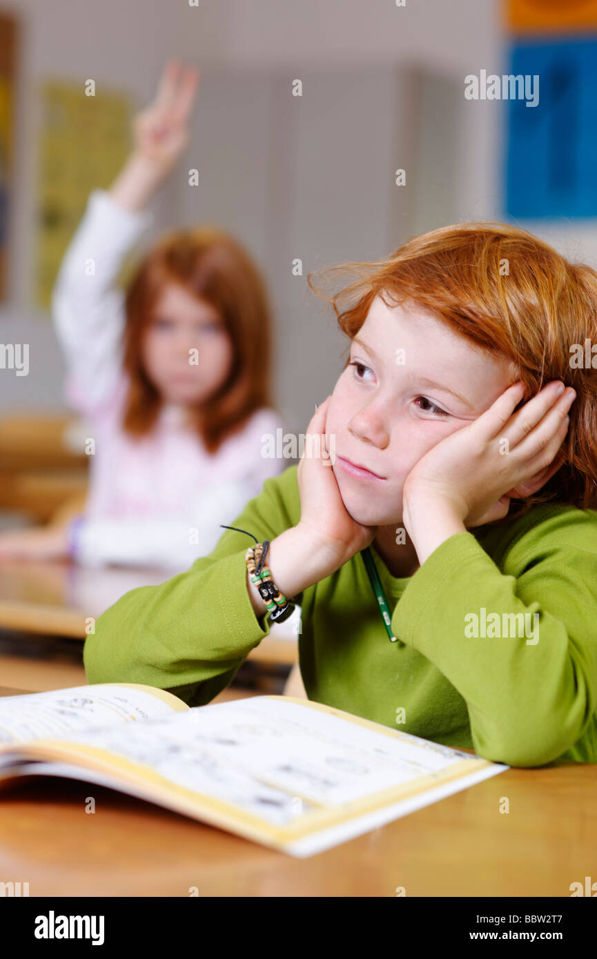 Children in a classroom in primary school, boy daydreaming or looking unsure, thoughtful, sad or frustrated, boys - Stock Image