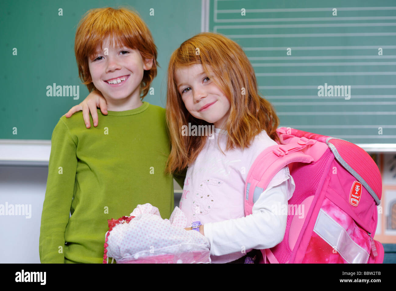 Two children in primary school, friends or siblings in a classroom - Stock Image