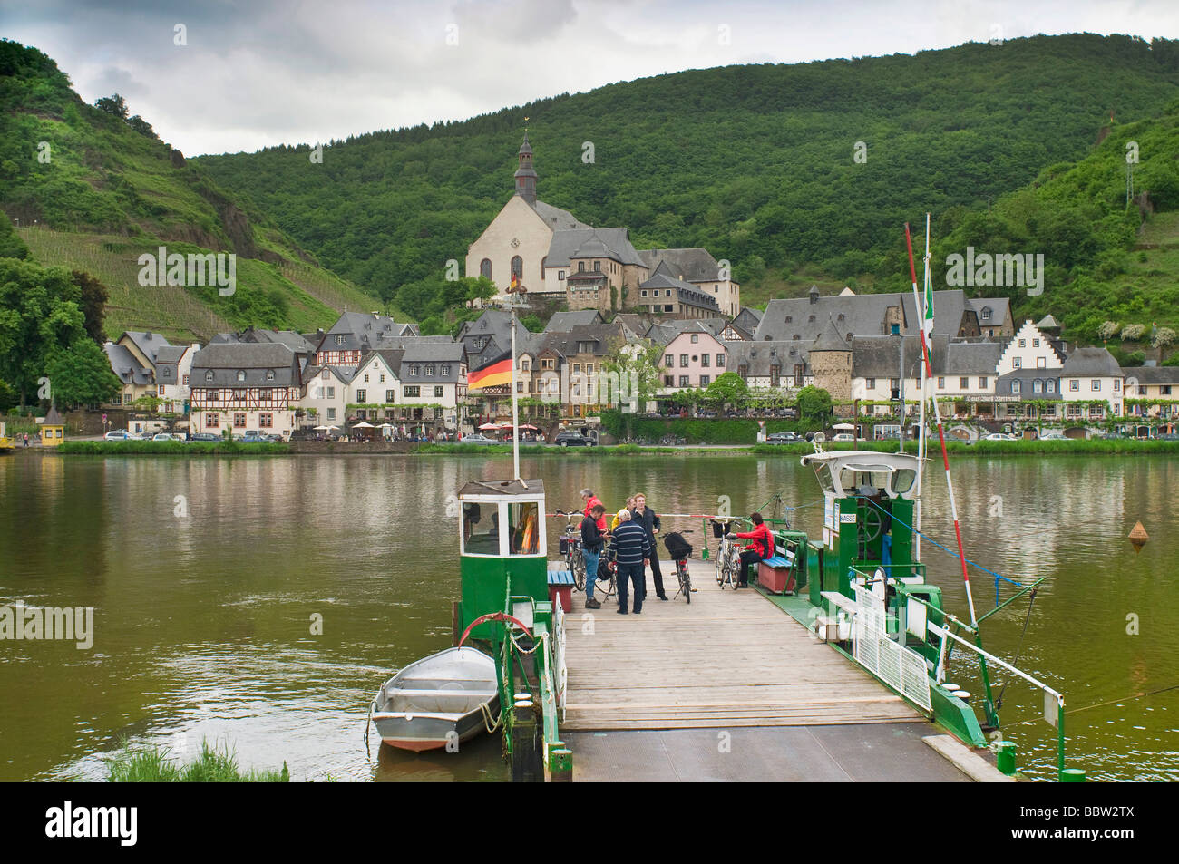 Beilstein Ferry on Mosel River, bikes and people on the ferry, Beilstein and St Josef abbey church in the back, - Stock Image