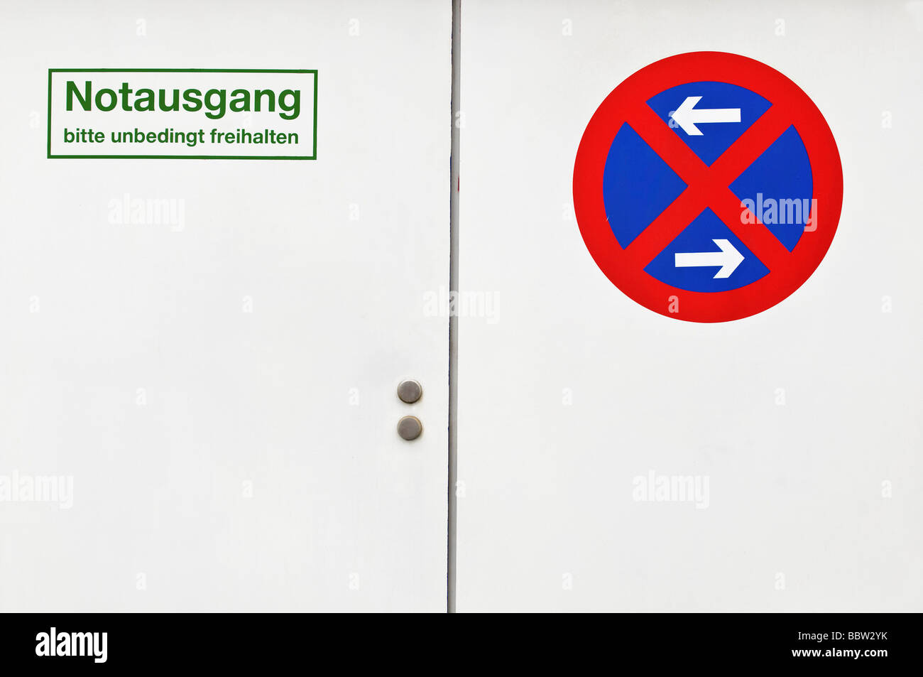 White door with emergency exit sign, do not block, stopping restriction on left and right - Stock Image