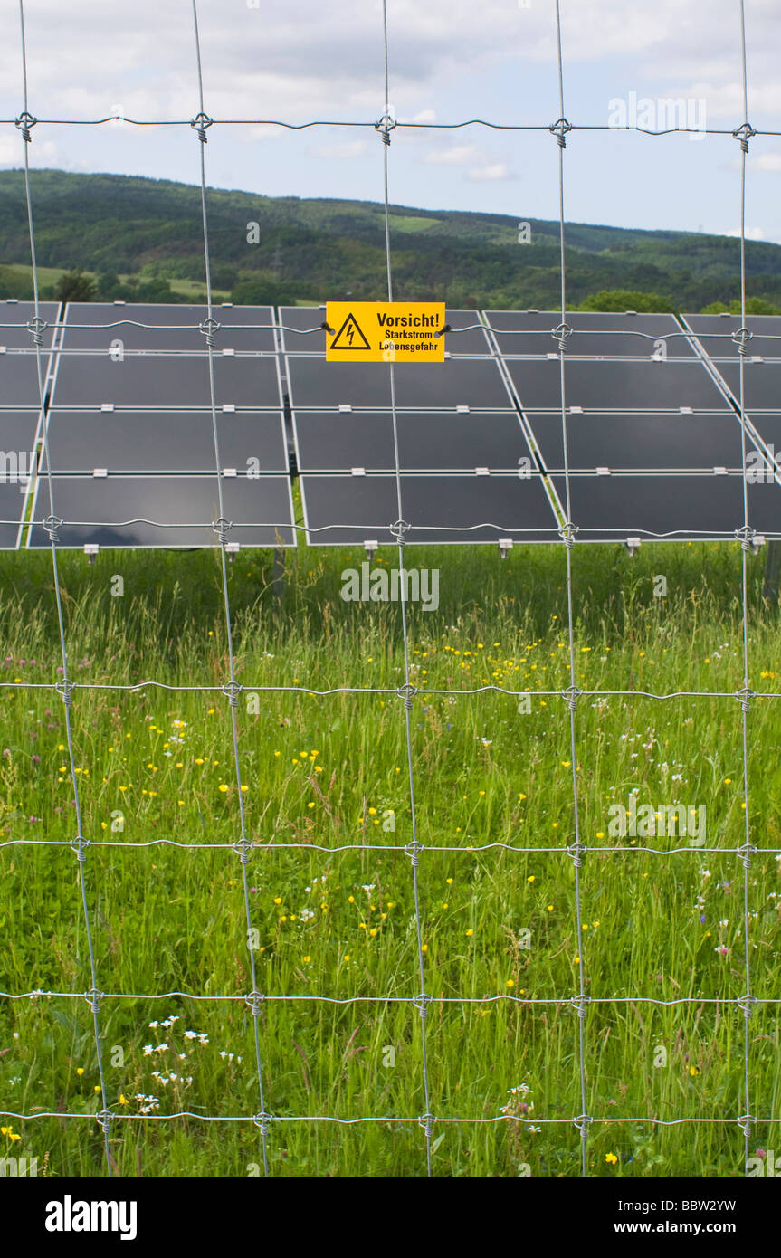 Photovoltaic power plant, several modules behind safety fence, warning sign, high voltage current, danger of life - Stock Image