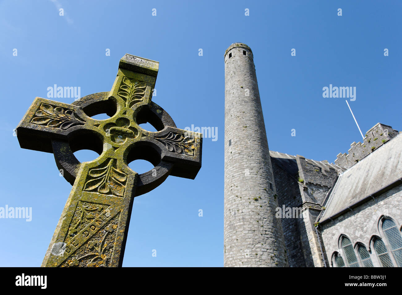 Celtic cross in front of Saint Canices cathedral and tower in Kilkenny city Southern Ireland - Stock Image