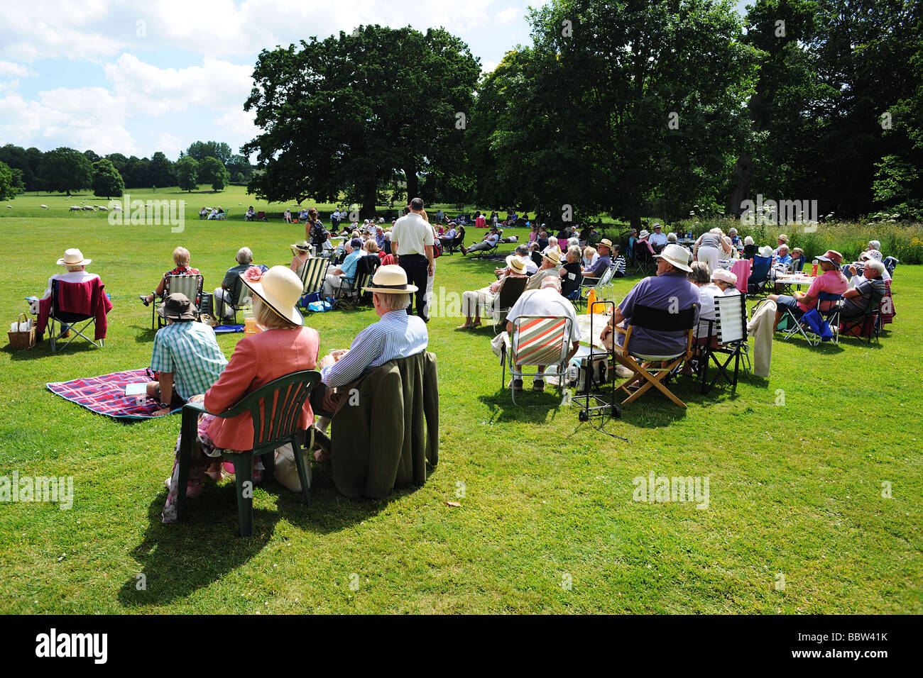 Crowd audience with picnic on a lawn in West Country England in the summer sun - Stock Image