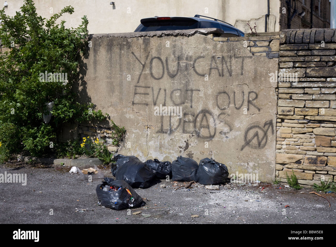 Orwellian graffiti sprayed left by evicted residents on rendered brick wall on now deserted estate wasteland - Stock Image