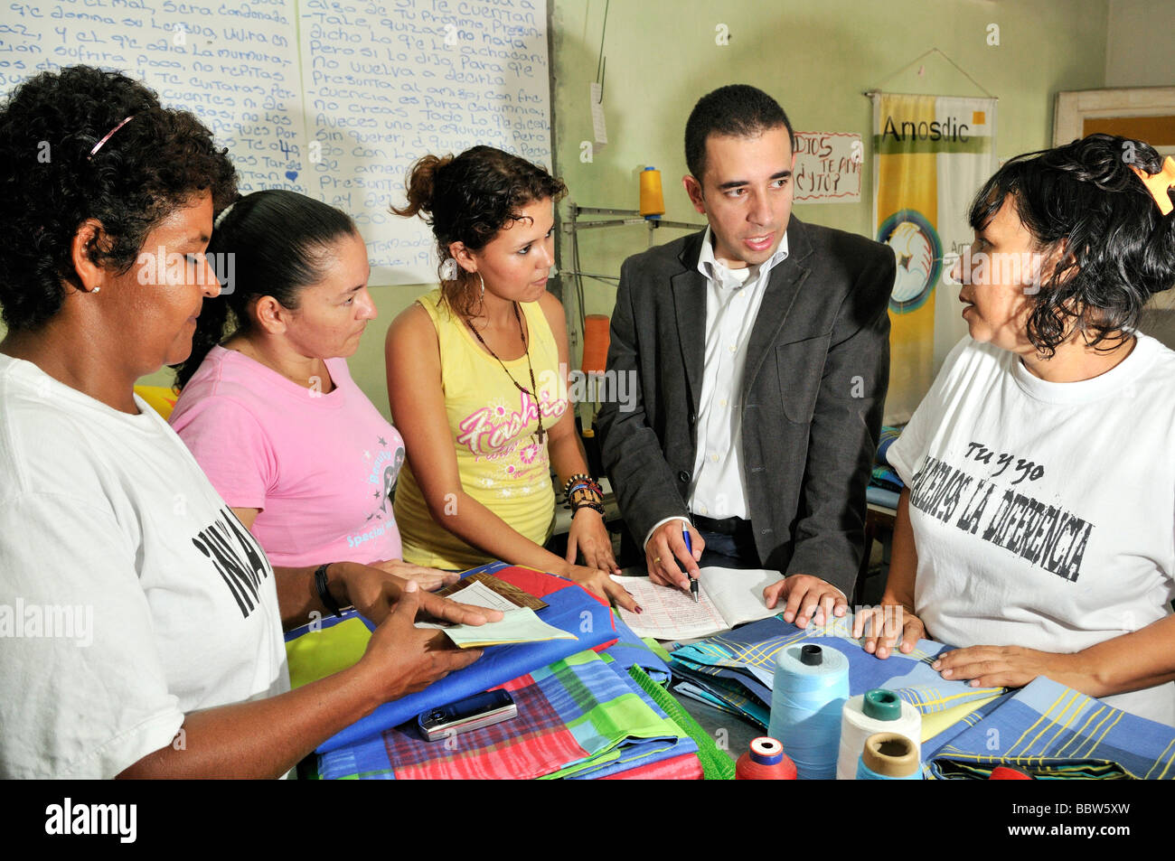 Development worker advising women about bookkeeping in a seamstress cooperative in La Dorada, Colombia, South America - Stock Image