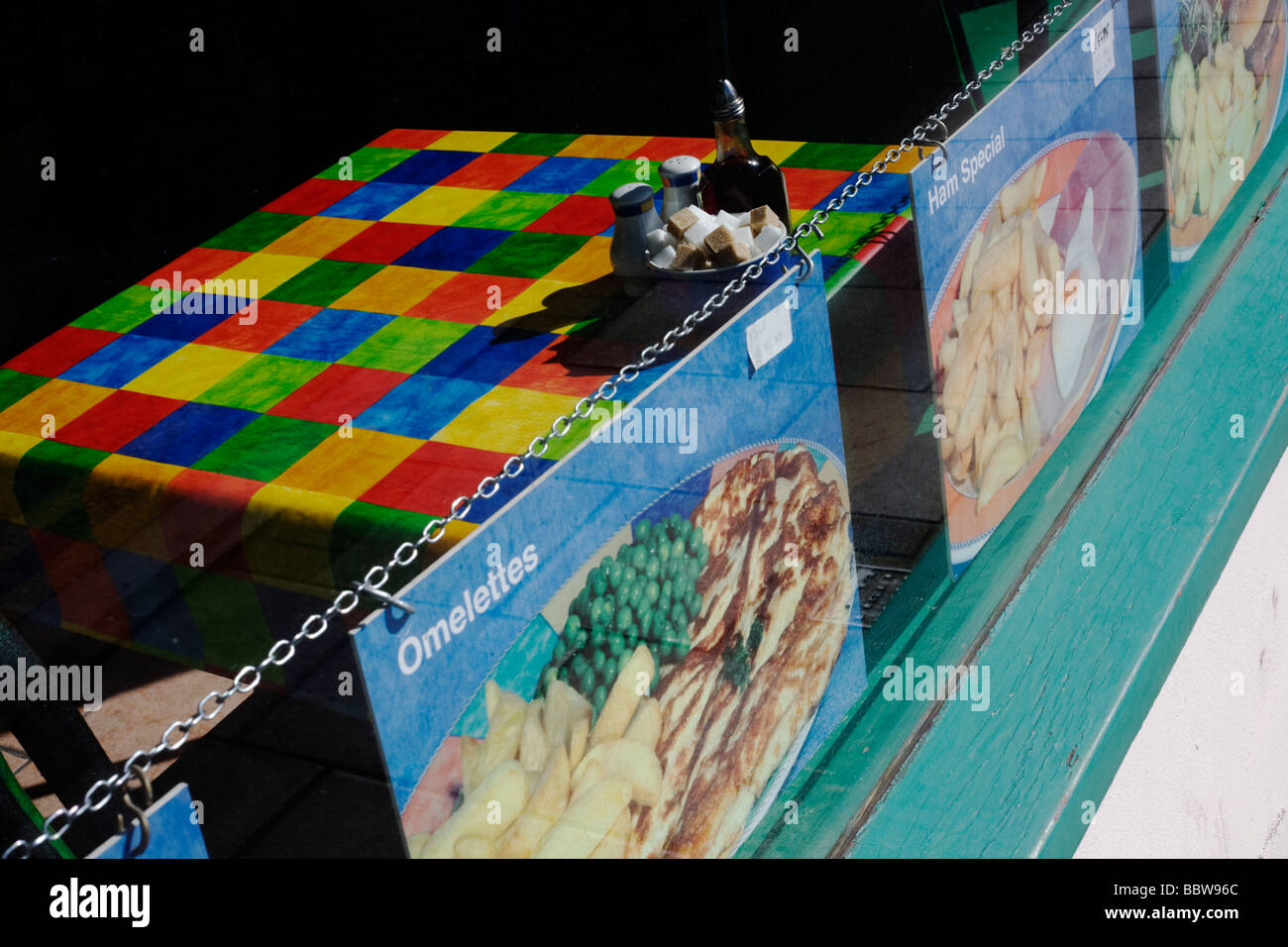 Brightly-coloured chequered table cloth and menu   in a seaside cafe window in Weston-super-Mare - Stock Image