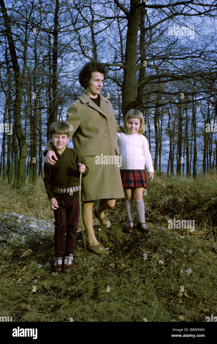 A 1960s mother stands for a family picture in woodland with her 5 year-old son and 4 year-old daughter - Stock Image