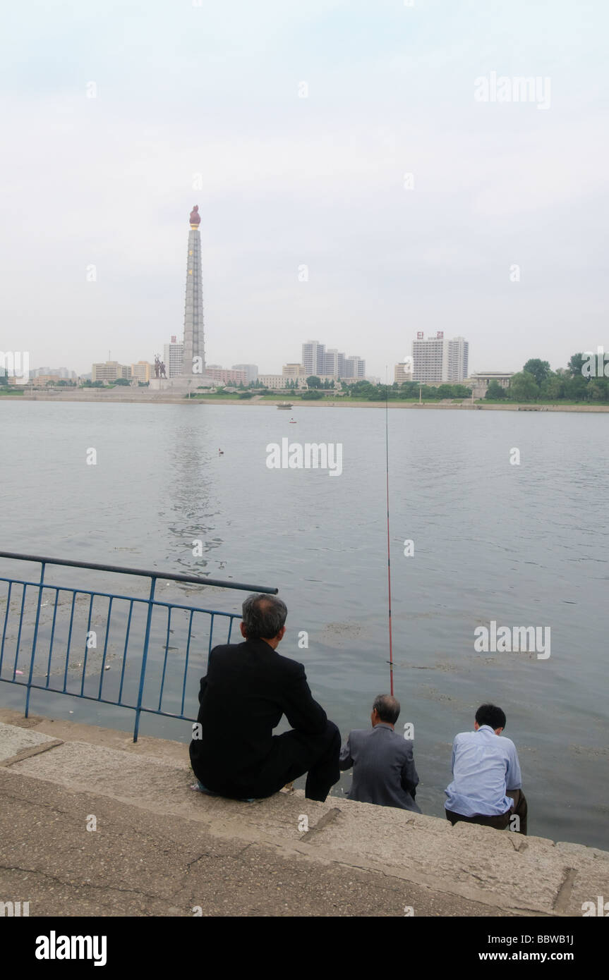 Fishing along the banks of the Taedong River in Pyongyang with the Tower of Juche Idea in background  - Stock Image