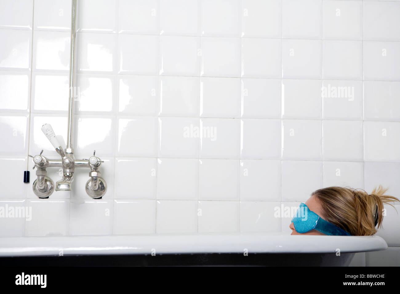 young woman in bathtub wearing an eye mask - Stock Image